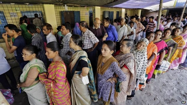 People stand in a queue to cast their vote at a polling station in Kamalgaji, on the outskirts of Kolkata, India, Monday, May 12, 2014.