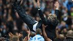 Players lift Manuel Pellegrini after winning the premier league title