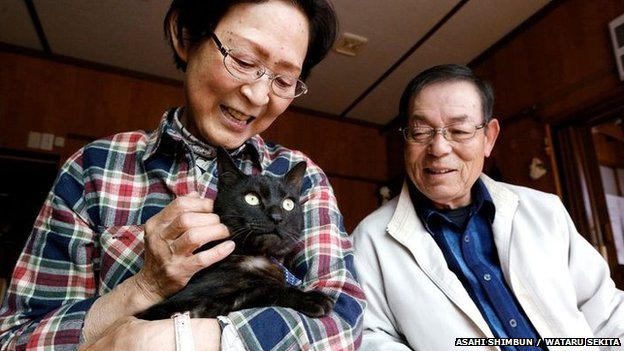 Kazuko and Takeo Yamagishi hold their cat Suika