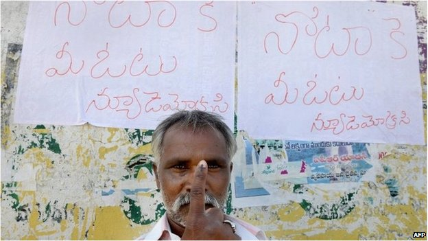 An Indian voter poses with his ink-marked finger in front of posters saying vote for None Of The Above