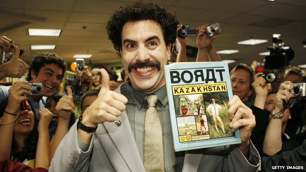 Sasha Baron Cohen dressed as Borat with fans behind him