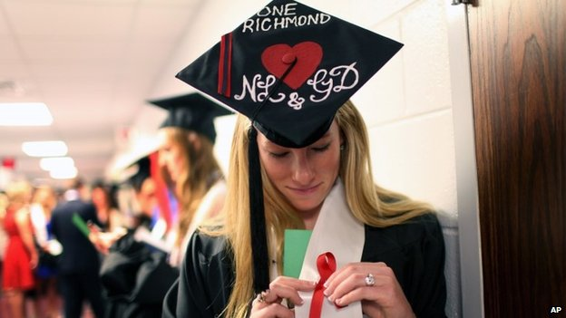 Laura Jordan wears a red ribbon with her hat decorated with initials of Natalie Lewis and Ginny Doyle before the University of Richmond's Commencement Ceremony in Richmond, Virginia 11 may 2014