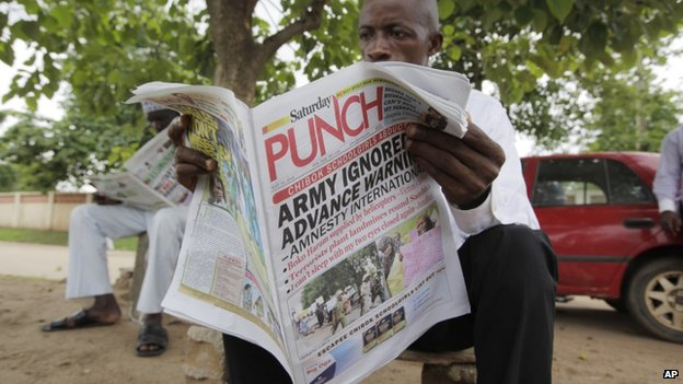 A man reads a local newspaper, with headlines stating the military was alerted four hours before abduction of secondary school Chibok girls, on a street in Abuja, Nigeria -  Saturday 10 May 2014