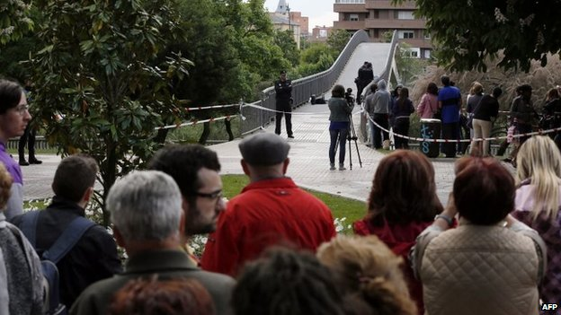 People look at police officers investigating at the site of the murder of Leon provincial council chief Isabel Carrasco in Leon, 12 May 2014