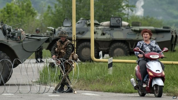 Woman rides scooter past Ukrainian army checkpoint near Luhansk. 12 May 2014