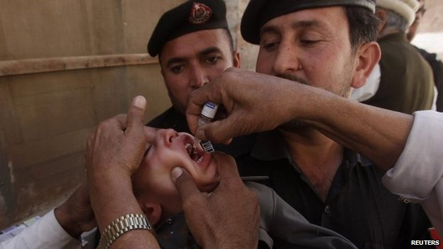 Polio workers give polio vaccine drops to a child as police stand guard during a vaccination campaign in Peshawar, the capital of Khyber-Pakhtunkhwa province March 30, 2014