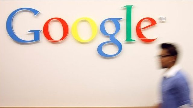 Man walks past Google sign