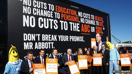 Ministers and Senators pose for media in front of a billboard showing an image of Prime Minister Tony Abbott at a ABC protest rally outside of Parliament House on May 13