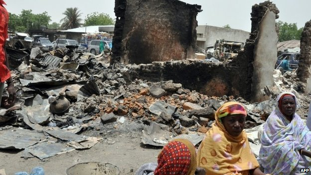 Women sit at Gamboru central market on 11 May  2014 burnt by suspected Boko Haram insurgents during the 5 May attack at Ngala in Gamboru Ngala district, Borno State in north-eastern Nigeria