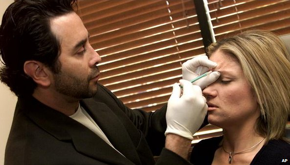 Man injecting Botox into woman's face