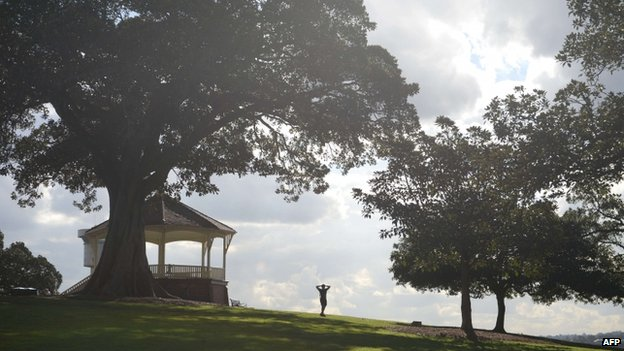 A runner walks down a hill in a park before sprinting back up again in Sydney on 13 May 2014