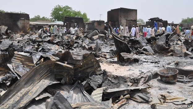 In this photo taken Sunday, May 11, 2014, people stand outside burnt houses following an attack by Islamic militants in Gamburo Nigeria