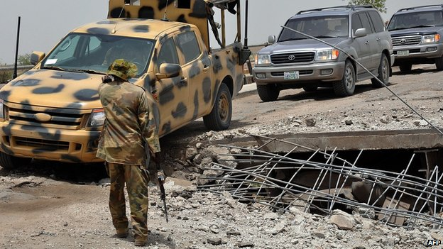 "A soldier directs the way to a military truck navigating through a link bridge at Ngala connecting Nigeria and Cameroon which was destroyed by suspected Boko Haram insurgents during last Monday""s attack at Ngala in Gamboru"