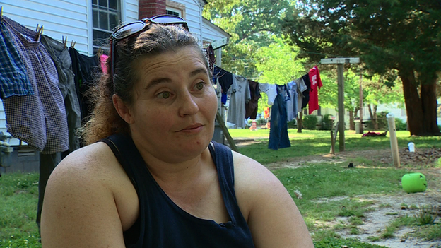 Woman sits in front of laundry on a line