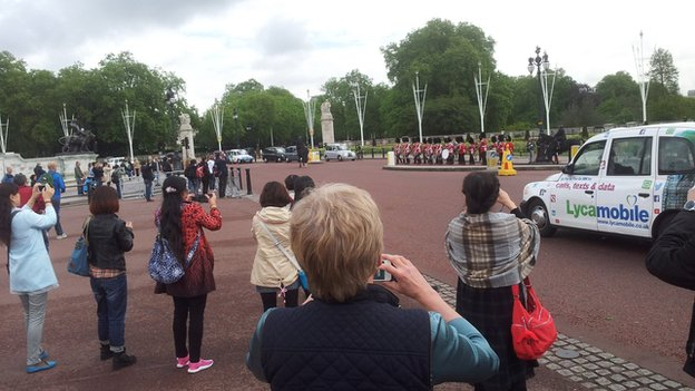 The BBC's China Editor Carrie Gracie photographs tourists snapping soldiers marching past Buckingham palace