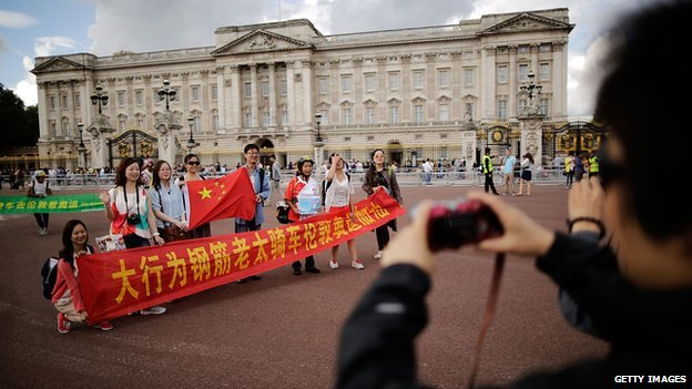 Chinese tourists have their pictures taken outside Buckingham Palace on 29 July, 2012 in London, England