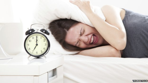 Alarm clock waking woman