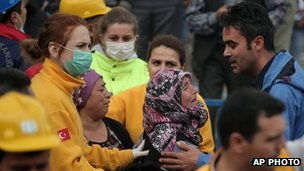 Family members react to news outside the mine