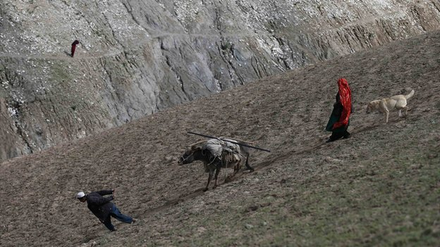 Villagers carry aid supplies on a donkey near the site of the Argo landslide