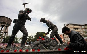 A man lays carnations at the Miners Monument in central Soma, Turkey on 14 May 2014