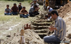 A man prays beside a grave of a dead miner in Soma on 14 May 2014