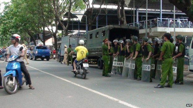 In this picture taken on 13 May, police officers stand with protective shields on the side of a street in Binh Duong, as anti-China protesters set factories on fire in Vietnam.