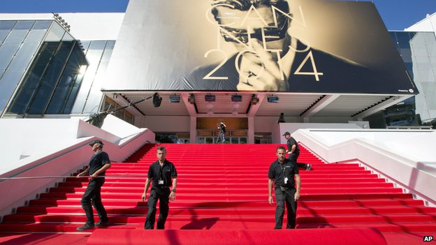 Workers prepare the red carpet on the stairs of the Palais des Festivals prior to the start of the 67th international film festival, Cannes