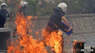Police officer running from a fire bomb