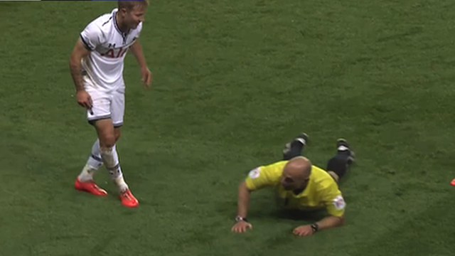 Referee Howard Webb after he was tackled by Tottenham's Lewis Holtby