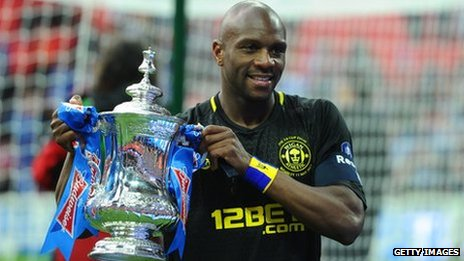 Wigan Athletic's Barbadian defender Emmerson Boyce poses with the FA Cup after beating Man City in the 2013 final