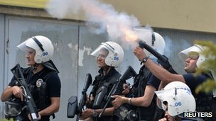 Police officer firing tear gas