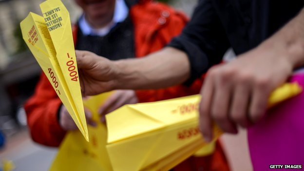 Supporters hold paper planes during a demonstration supporting a minimum wage of 4000 Swiss francs on May 7, 2014 in Geneva