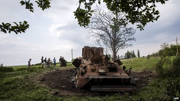 Youths look at a destroyed Ukrainian army vehicle near Kramatorsk in eastern Ukraine - 14 May 2014