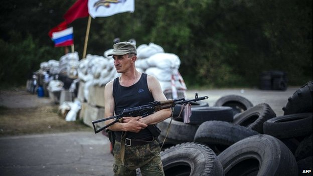 An armed pro-Russian militant stands guard at a barricade near Luhansk - 14 May 2014