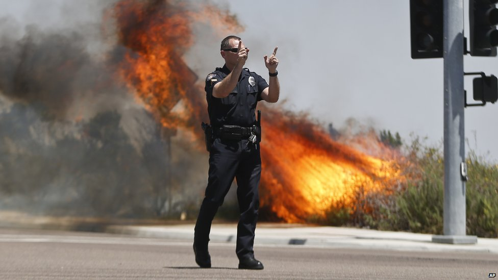 A police officer directed traffic away from flames in Carlsbad, California, on 14 May 2014