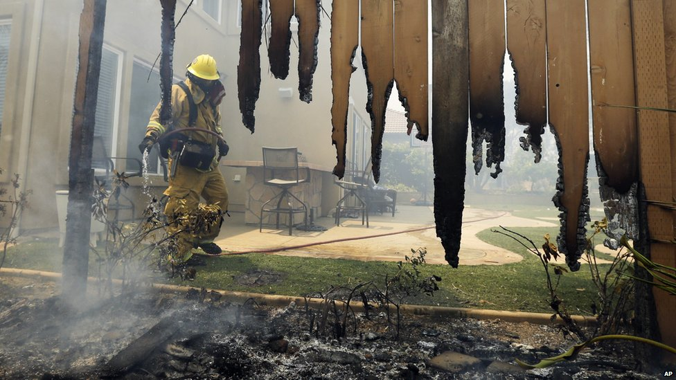 A firefighter put water on a house fence during a wildfire in Carlsbad, California, on 14 May 2014