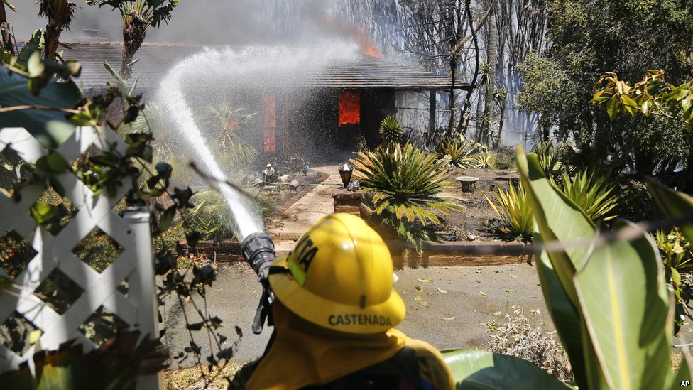 A fire fighter poured water onto a fully engulfed home in Carlsbad, California, on 14 May 2014