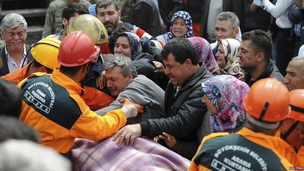 People react as rescuers carry the body of a man out of the mine in Soma - 14 May 2014