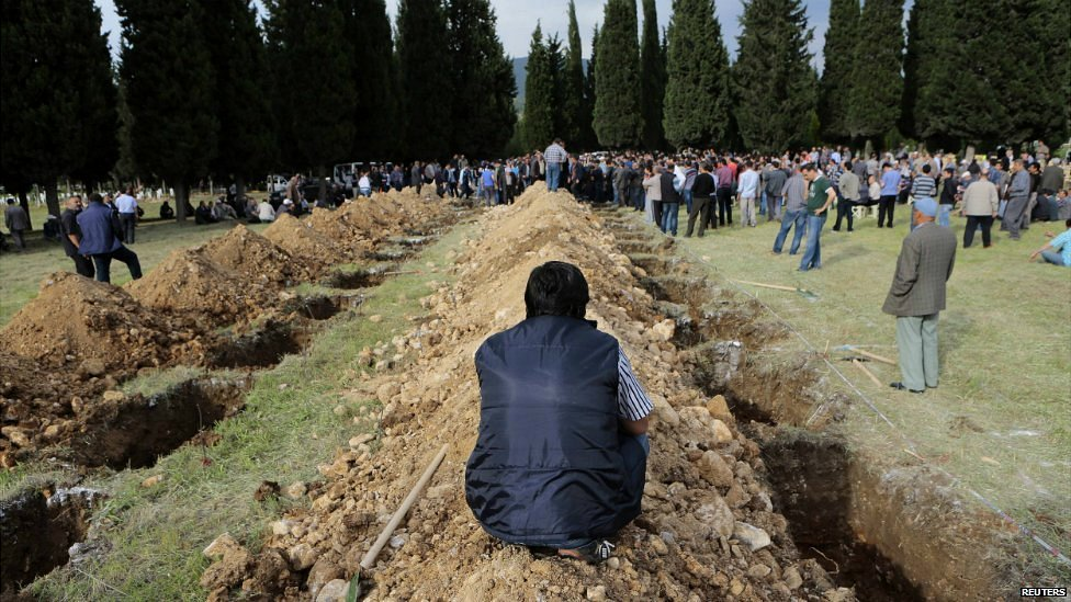 A man sits near graves during the funeral of a miner who died in disaster in Soma - 14 May 2014