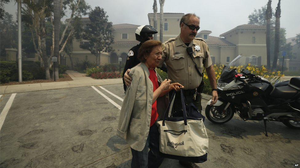 A woman was evacuated from her building during a wildfire in Carlsbad, California, on 14 May 2014