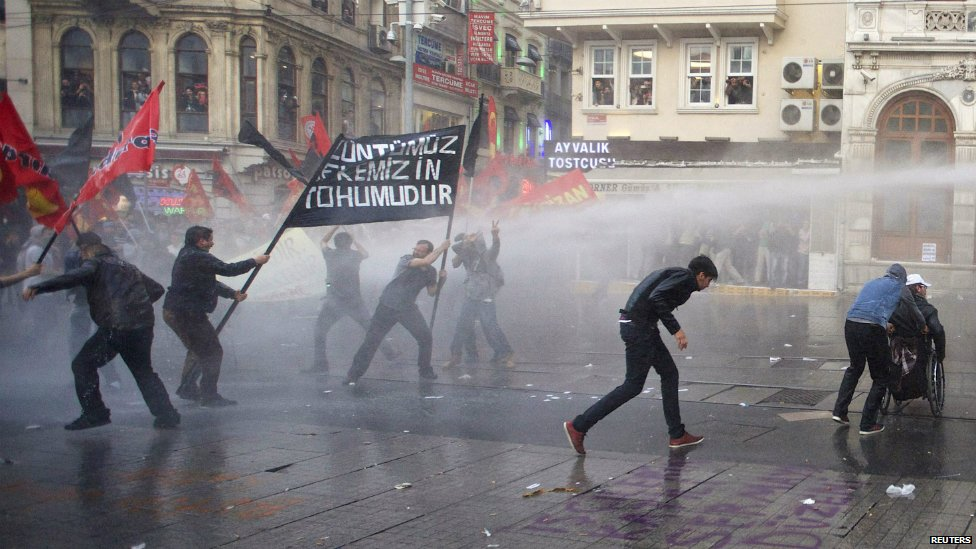 Protesters run away from water cannon fired by riot police during a demonstration in Istanbul - 14 May 2014