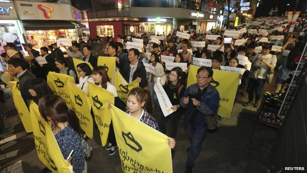 People march on a street after attending a candlelight vigil to commemorate victims of the sunken Sewol passenger ferry, and to denounce the South Korea government's handling of the disaster, in central Seoul on 10 May 10.