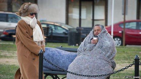 A woman walks by a homeless man in Washington DC