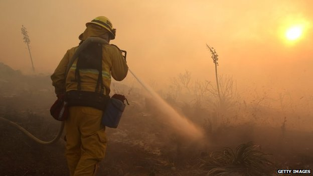 A firefighter puts down hot spots in front of a house in the hills in San Marcos, California, 1 May 2014