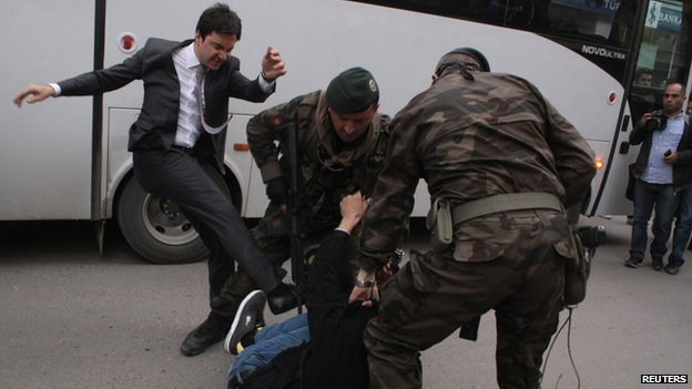 Erdogan aide Yusuf Yerkel (left) kicks a protester in Soma, Turkey, on 14 May 2014