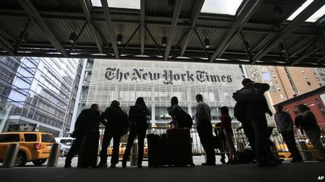 Pedestrians wait for taxis across the street from The New York Times in New York, 14 May 2014
