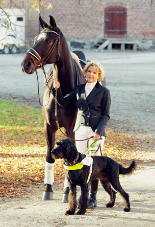 Verity Smith holding her horse and her guide dog Uffa
