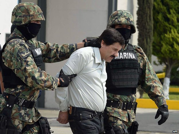 Mexican drug trafficker Joaquin Guzman Loera aka 'el Chapo Guzman' (C), is escorted by marines as he is presented to the press on February 22, 2014 in Mexico City
