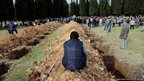 A man sits near graves during the funeral of a miner who died in a fire at a coal mine in Soma