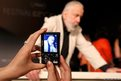 A journalist takes a picture as director Mike Leigh